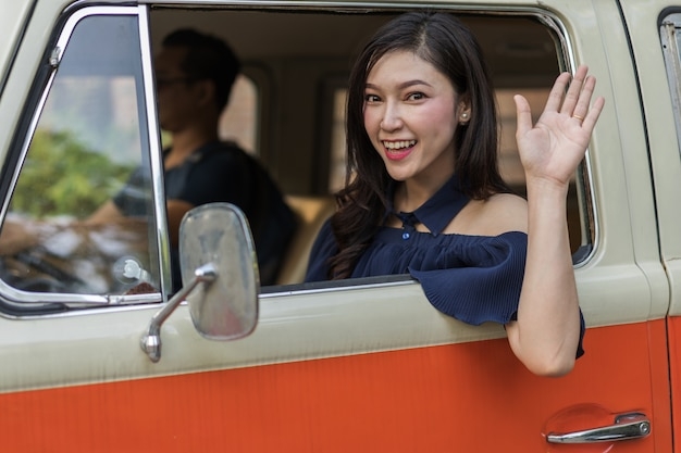 Happy woman vintage window of old car and raising her hand