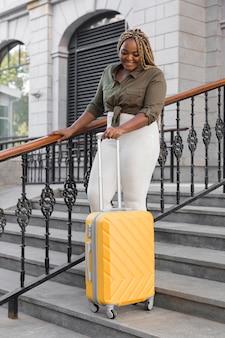 Счастливая женщина, идущая по лестнице с багажом