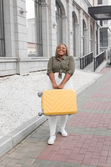 Happy woman walking while holding a luggage