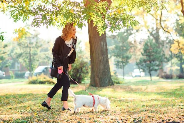 Счастливая женщина гуляет со своим маленьким вест-хайленд-уайт-терьером в парке
