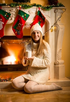 Happy woman in warm sweater and hat sitting at fireplace with tea cup