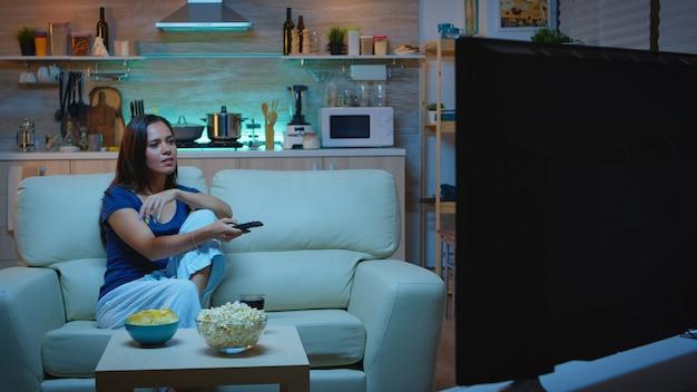 オープンスペースのリビングルームで快適なソファに座ってジュースを飲むテレビを見ている幸せな女性。興奮し、面白がって、夜遅くに一人で家に帰り、リモコンでチャンネルを変えるテレビでリラックス。