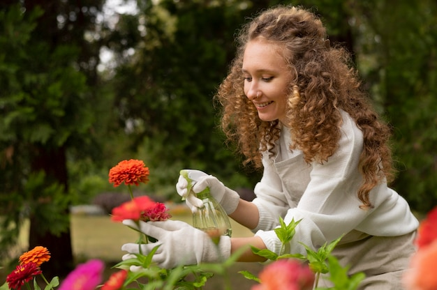 Donna felice che innaffia il fiore, colpo medio