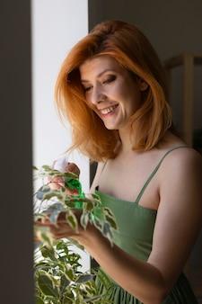 Donna felice che innaffia la pianta a colpo medio