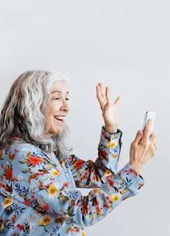 Happy woman waving hello to a smartphone