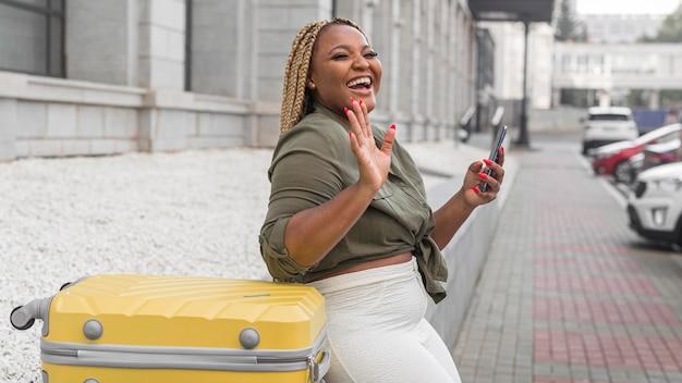 Счастливая женщина машет, стоя рядом с ее багажом