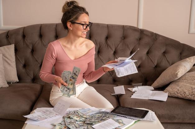Счастливая женщина в черных очках, глядя на счета