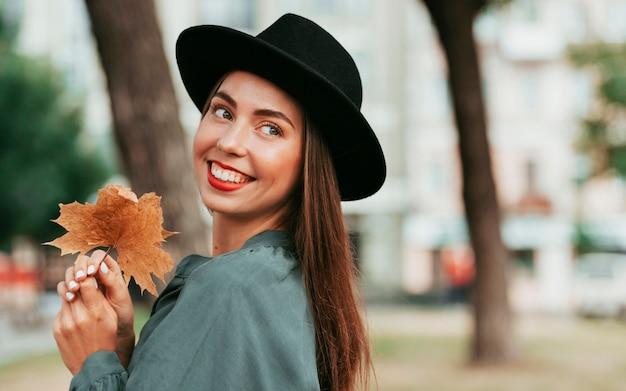 Felice donna che indossa un cappello nero mentre guarda lontano