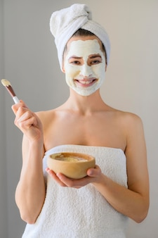 Happy woman wearing face mask and holding bowl