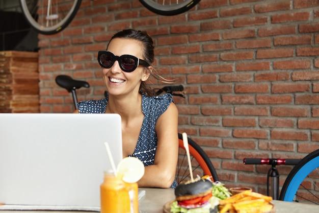 Счастливая женщина в модных оттенках обедает в кафе и использует портативный компьютер, ожидая друзей в солнечный день