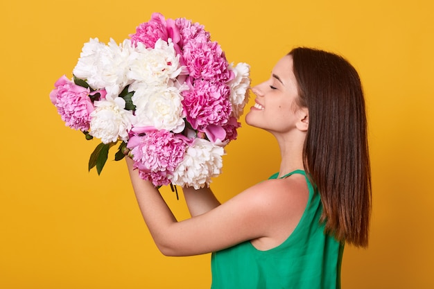 Happy woman wearing green attire holding and smelling white and pink peonies flowers