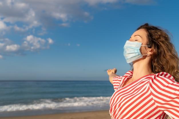 푸른 하늘 배경에 야외 의료 마스크를 착용하는 행복 한 여자. 여름에 바다로 즐기는 사람.