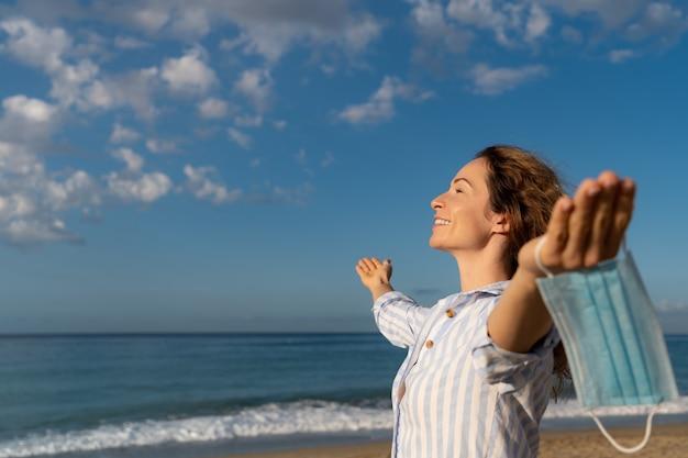 푸른 하늘 배경 야외 의료 마스크를 쓰고 행복 한 여자