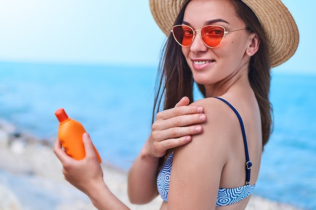 Happy woman wearing swimsuit, straw hat and bright red sunglasses apply sunscreen on her shoulder during relaxing and sunbathing by the sea in sunny weather in summertime