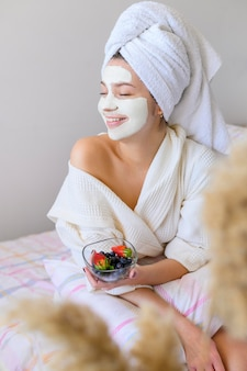 Happy woman wearing towel on head and face mask