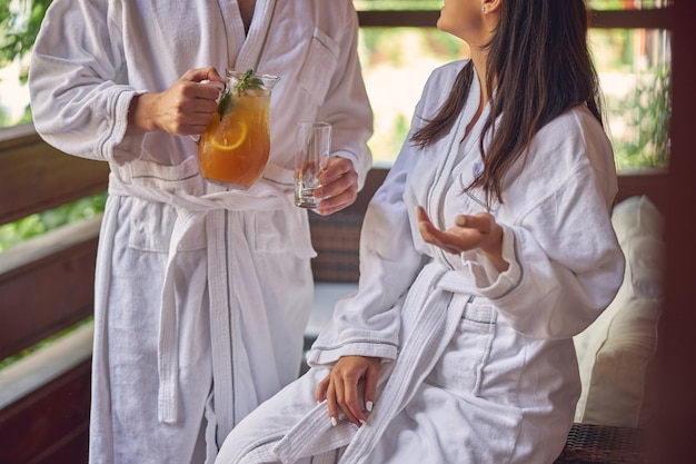 그는 오렌지 레모네이드를 손에 들고있는 동안 흰색 부드러운 목욕 가운과 남자를 입고 행복한 여자