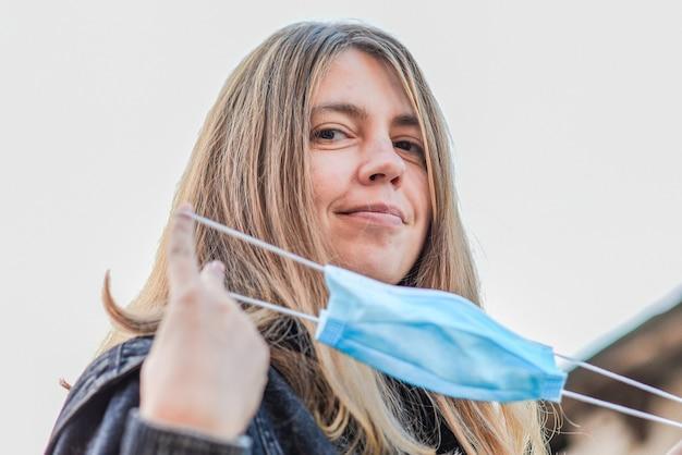Счастливая женщина носит медицинскую маску, потому что загрязнение воздуха или вирус - это эпидемия в городе.