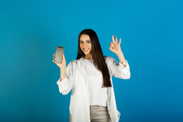 Happy woman wears casual outfit holds mobile phone and makes okay gesture on blue