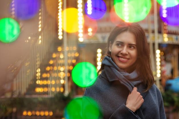 幸せな女性はボケの光で通りを歩いて灰色のコートを着ています。空きスペース
