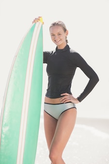 Happy woman in wetsuit holding a surfboard on the beach