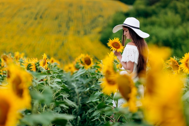Happy woman in a white dress and hat in a field of sunflowers enjoys the sunlight. summer walk on the field of sunflowers of a young girl. selective focus