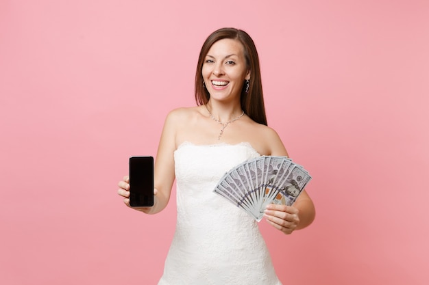 Happy woman in white dress holding bundle lots of dollars, cash money, mobile phone with blank black empty screen