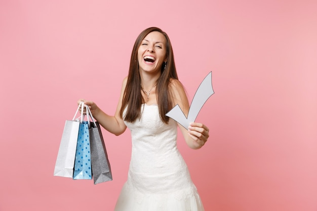 Happy woman in white dress holding check mark, multi colored packages bags with purchases after shopping