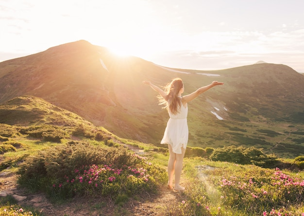 Happy woman in white dress with raised hands enjoying mountains landscape a sunset time
