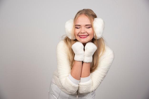 Donna felice in abito bianco in posa per la macchina fotografica.