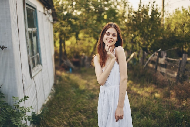 Happy woman in a white sundress near the building in nature and trees in the background.