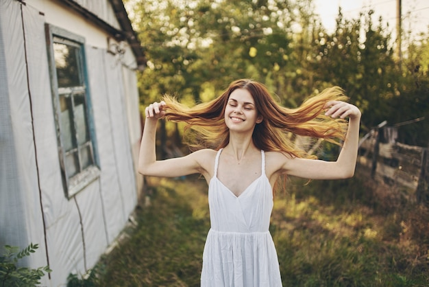Happy woman in a white sundress near the building in nature and trees in the background