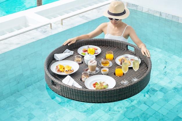 Happy woman in white swimsuit having floating breakfast tray in luxury pool hotel