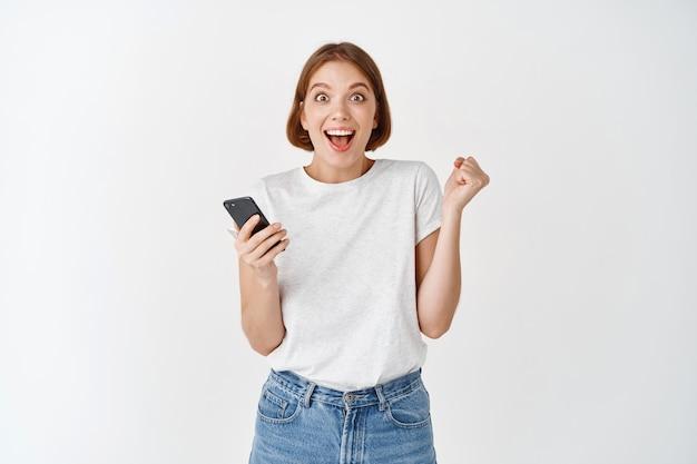 スマートフォンのビデオゲームで勝つ幸せな女性、手を上げて応援し、喜びでイエスと叫び、オンライン目標を達成し、白い壁に立って