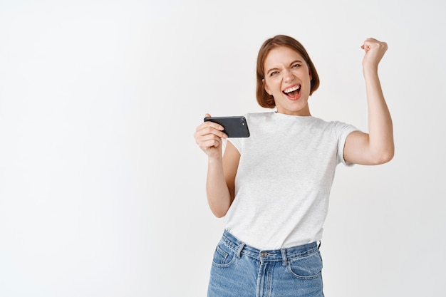 Happy woman winning on smartphone video game, raising hand up and cheering, shouting yes with joy, achieve online goal, standing on white wall