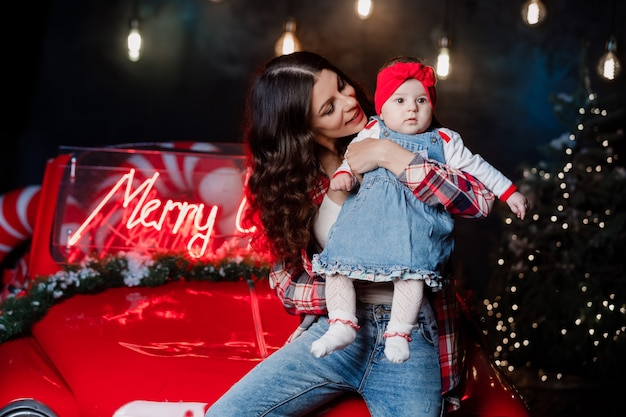 Счастливая женщина с девочкой с красным бантом на голове сидят и веселятся на ретро-машине с рождественскими украшениями