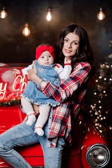 머리에 붉은 활과 아기 소녀와 함께 행복 한 여자는 앉아서 크리스마스 장식과 함께 복고풍 자동차에 재미