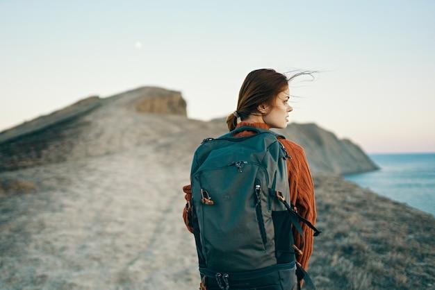自然の新鮮な空気の中で海の近くの山の小道に沿って歩くバックパックを持つ幸せな女性