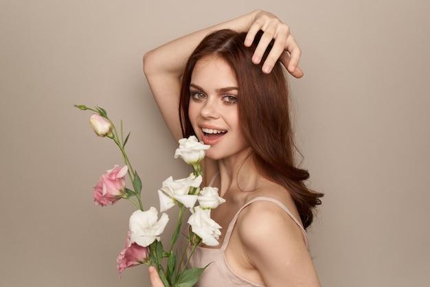 베이지 색 벽에 밝은 꽃의 꽃다발과 함께 행복 한 여자 벗은 어깨 모델 빨간 머리 아름다운 얼굴.