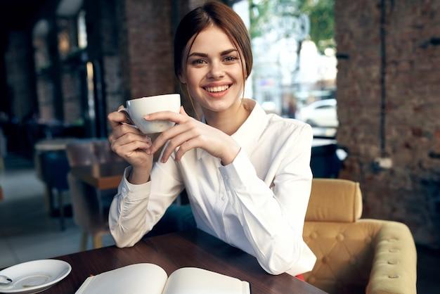 手にカップを持つ幸せな女性は、レストランとインテリアの椅子に座っています