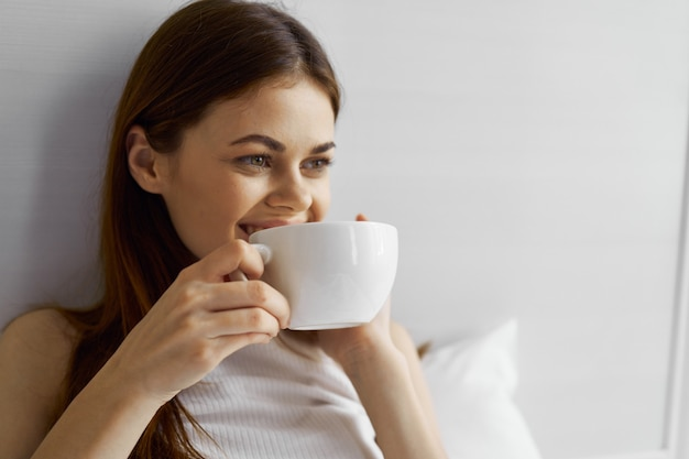 Счастливая женщина с чашкой кофе лежит в постели и смотрит в сторону крупным планом
