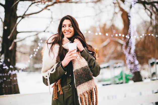 Счастливая женщина с чашкой горячего напитка холодной зимой на открытом воздухе на рождественской ярмарке