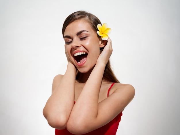 彼女の髪に花を持つ幸せな女性彼女の手で別の頭と彼女の口を大きく開いた喜び