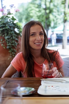 카페테리아의 여름 테라스에서 빨간 주스 한 잔을 들고 행복한 여자.