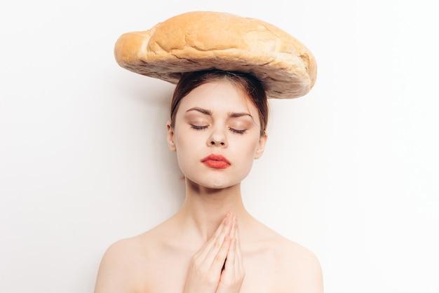彼女の手の瞑想とメイクモデルで身振りで示す彼女の頭にパンを持つ幸せな女性