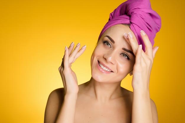 머리에 수건을 얹은 행복한 여성은 노란색 배경의 얼굴에 크림을 바르고 있다