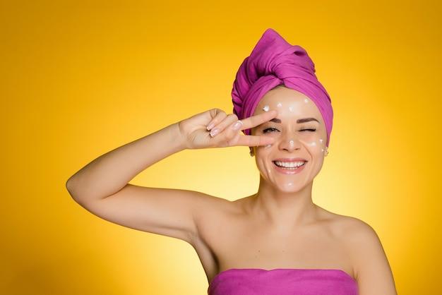 머리에 수건을 두른 행복한 여자는 얼굴에 크림을 바르고 있다