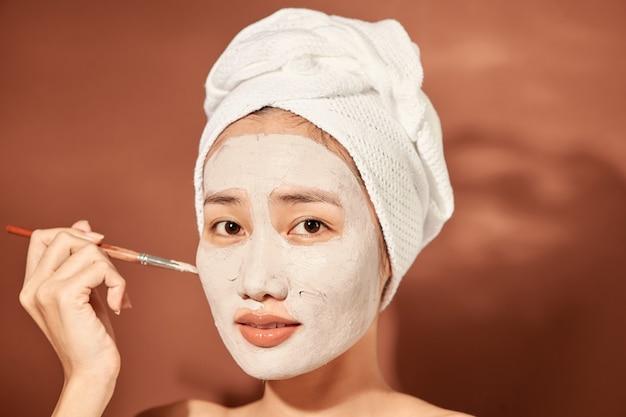 彼女の頭にタオルを持っている幸せな女性は彼女の顔にクレンジングマスクを適用します