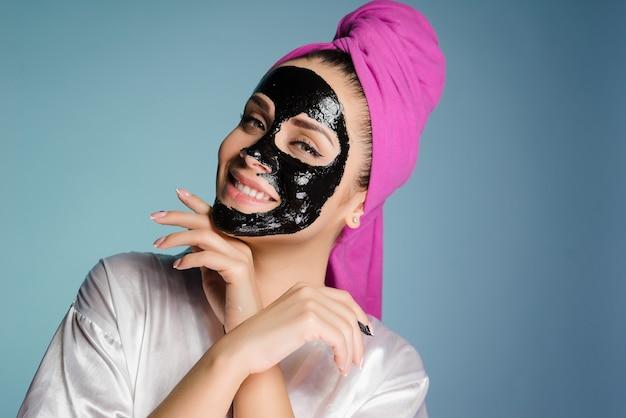 頭にタオルを持った幸せな女性が顔の皮膚にクレンジングマスクを適用します