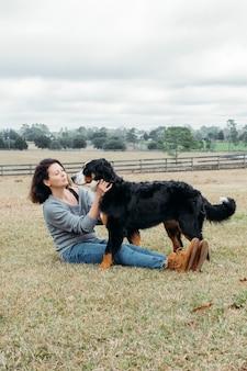 Счастливая женщина с активной собакой, играющей на открытом воздухе веселый хозяин и большая бернская горная собака развлекаются на поле на фоне деревенского пейзажа прогулка с домашним животным