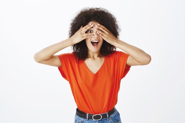 Счастливая женщина с афро прической позирует в студии